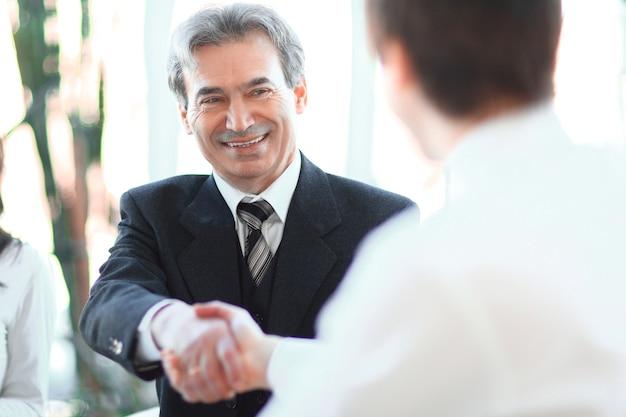 Zbliżenie. handshake manager i klient siedzi przy biurku w biurze. zdjęcie z miejscem na kopię