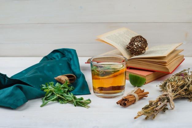 Zbliżenie herbaty ziołowej i kwiatów z książkami, cytryną, przyprawami i zielonym szalikiem