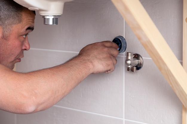 Zbliżenie hydraulika męski pracownik w błękitnym drelichu mundurze, kombinezony, naprawia zlew w łazience z płytki ściennej. profesjonalny serwis naprawczy instalacji wodociągowej, instalacja kanalizacyjna montowana przez człowieka