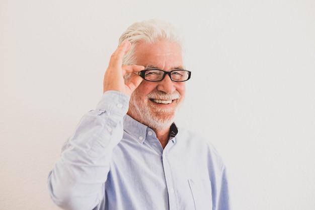 Zbliżenie i portret dojrzałego mężczyzny uśmiechającego się i patrzącego w kamerę z białą ścianą w tle - aktywna koncepcja seniora i styl życia - emeryt intelektualny i inteligencja w okularach