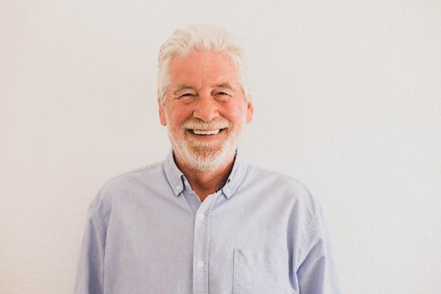 Zbliżenie i portret dojrzałego mężczyzny uśmiechającego się i patrzącego w kamerę z białą ścianą w tle - aktywna koncepcja seniora i styl życia