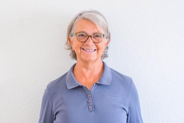 Zbliżenie i portret dojrzałej kobiety uśmiechniętej i patrzącej w kamerę z białą ścianą w tle - aktywna koncepcja seniora i styl życia