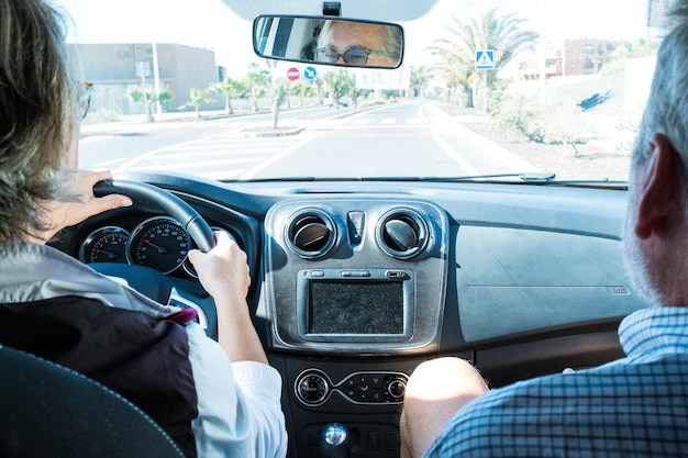 Zbliżenie i portret dwóch dojrzałych ludzi w samochodzie, patrząc na drogę lub ulicę - emeryt senior jazdy samochodem i mężczyzna siedzący obok niej