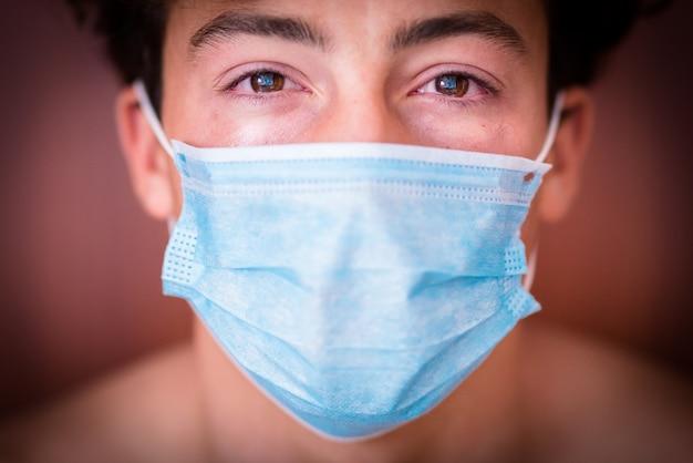 Zbliżenie i portret jednego tysiącletniego nastolatka patrzącego w kamerę smutnego, noszącego reklamę w masce płaczącej za covid-19