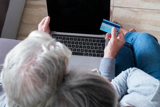 Zbliżenie i powyżej oraz widok z góry dwóch seniorów i emerytów w domu na kanapie robiących zakupy online razem z kartą kredytową - dojrzały mężczyzna trzymający kartę kredytową i używający laptopa