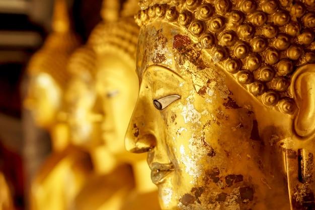 Zbliżenie i przycinanie starej i złotej twarzy złotego posągu buddy na niewyraźnym złotym posągu buddy stoją na tle silnej linii
