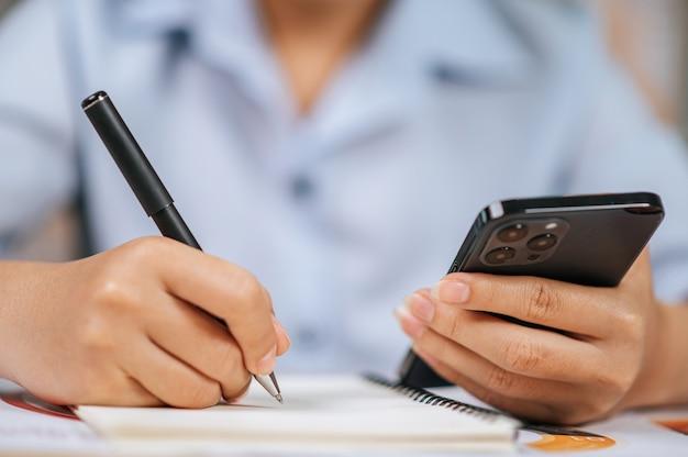 Zbliżenie i selektywne skupienie ręka azjatyckiej młodej kobiety w okularach używa pióra pisania na papierach w domowym biurze, podczas kwarantanny covid-19 samodzielna izolacja w domu, praca z koncepcji domu