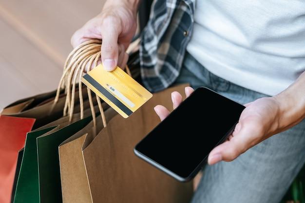 Zbliżenie i selektywne skupienie, ręka mężczyzny trzymająca wiele toreb na zakupy