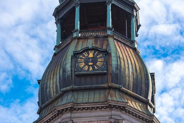 Zbliżenie iglicy z zegarem kościoła św piotra, stare miasto w rydze, łotwa