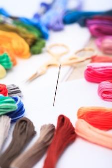 Zbliżenie igły do haftu, kolorowej nici i nożyczek na płótnie