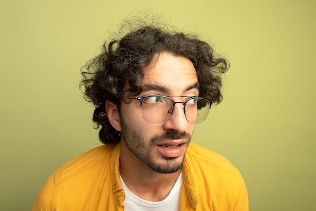 Zbliżenie: imponujący młody przystojny kaukaski mężczyzna w okularach, patrząc na bok na białym tle na oliwkowej ścianie