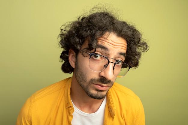 Zbliżenie: imponujący młody przystojny kaukaski mężczyzna w okularach, patrząc na kamery na białym tle na oliwkowym tle