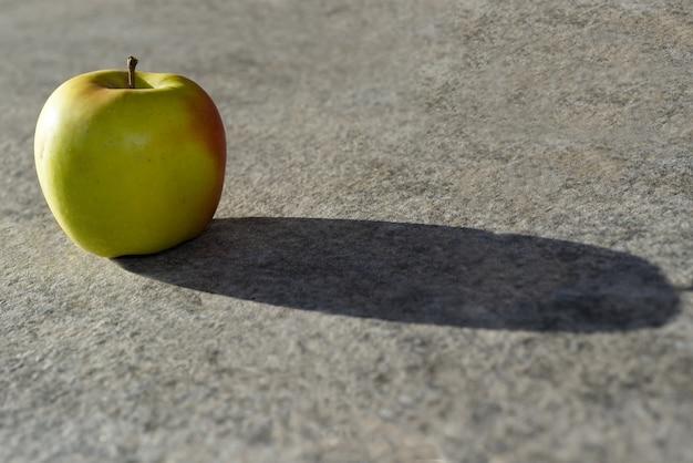 Zbliżenie jabłka i jego cień na powierzchni betonu