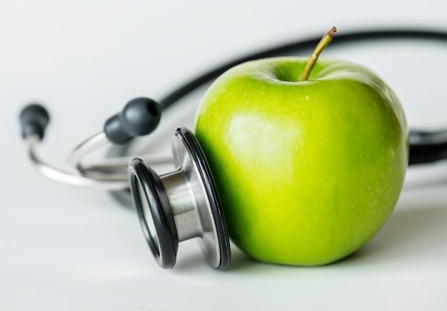 Zbliżenie jabłka i stetoskopu zdrowy jedzenie i zdrowia pojęcie