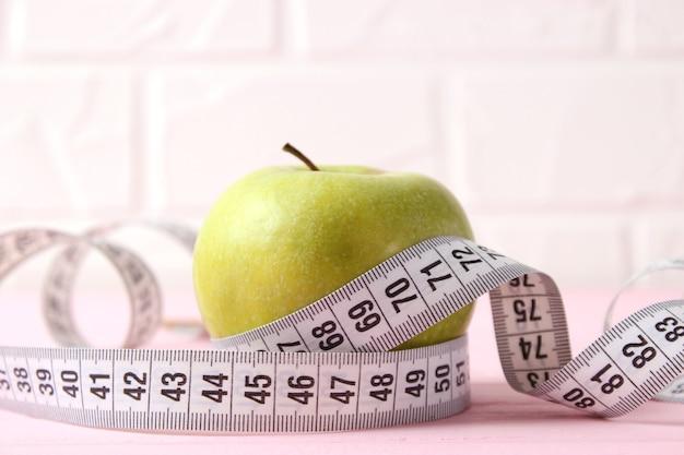 Zbliżenie jabłko i taśma miernicza na jasnym tle