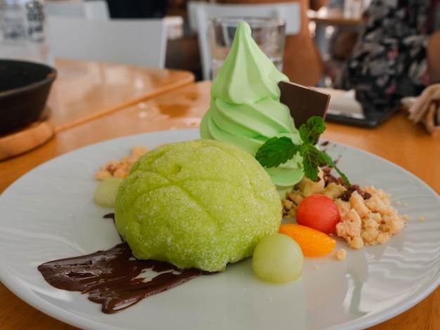 Zbliżenie japoński styl zielony chleb mellon z miękką śmietaną i sosem czekoladowym na stole, słodki deser
