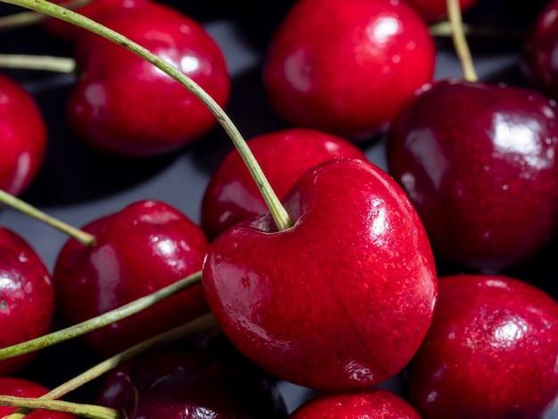 Zbliżenie: jasne soczyste świeże wiśnie na ciemnym tle. pyszne i zdrowe jagody, zdrowa żywność, wegetarianizm