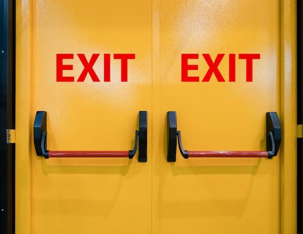 Zbliżenie jasne, żywe żółte podwójne drzwi do wyjścia awaryjnego