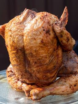 Zbliżenie jasnego, soczystego kurczaka w przyprawach, gotowane w całości na grillu. rozmyte zielone tło. obrazy poziome