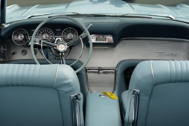 Zbliżenie jasnoniebieskiego wnętrza samochodu, w tym siedzeń i kierownicy