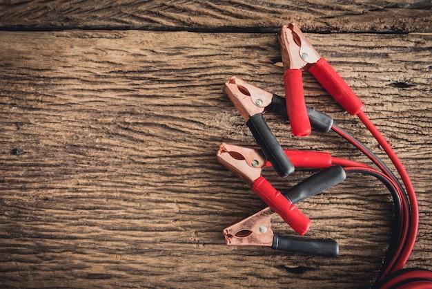 Zbliżenie kabel skoczka do akumulatora samochodowego na drewniane tła