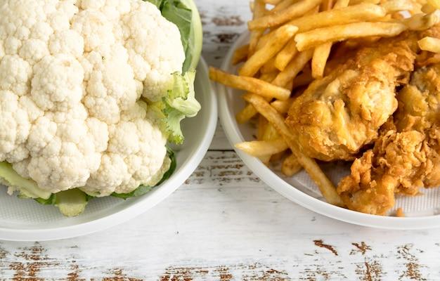 Zbliżenie kalafiora i smażone jedzenie na stole