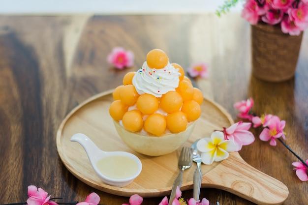 Zbliżenie kantalupa bingsu na tacy, bingsu lub bingsoo, koreański deser lodowy ogolone z słodkie polewy
