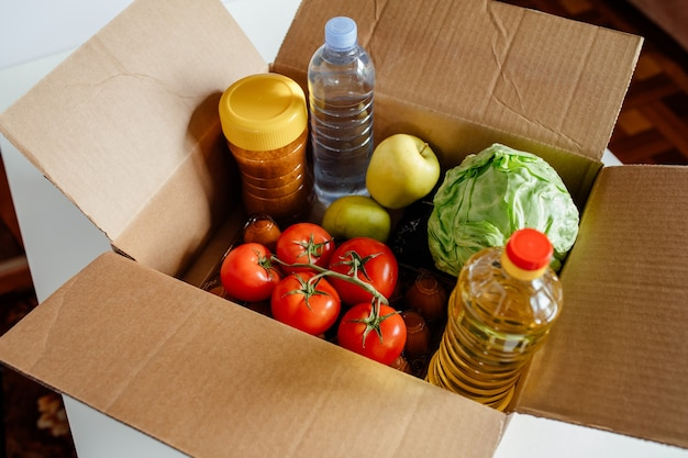 Zbliżenie karton z różnymi świeżymi pakowanymi produktami spożywczymi koncepcja bezpiecznej dostawy żywność społeczna do...