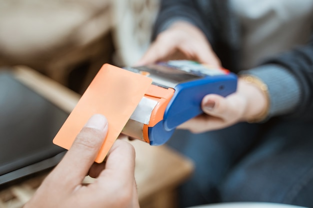 Zbliżenie karty kredytowej w pobliżu urządzenia do elektronicznego przechwytywania danych podczas zakupów w sklepie
