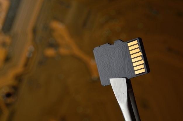 Zbliżenie karty pamięci micro sd na tle mikroukładu, zaciśniętego pęsetą.