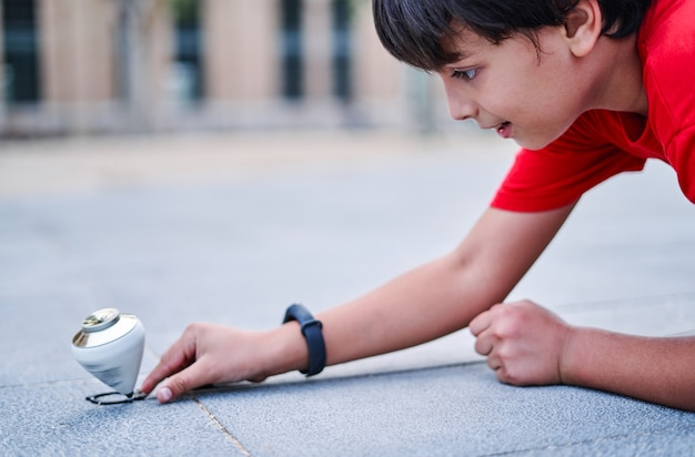 Zbliżenie kaukaski chłopiec bawi się bączkiem w parku.