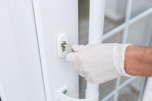 Zbliżenie kaukaski mężczyzna otwierający drzwi kluczem w lateksowych rękawiczkach, koncepcja higieny.