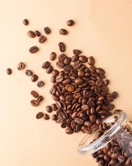 Zbliżenie kawowe fasole rozlewają się z szklanego słoju na jasnobrązowym tle. do palarni, kawiarni i kawiarni.