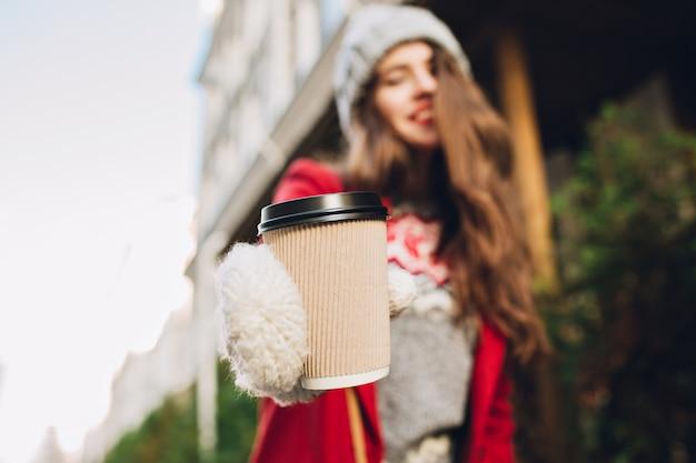 Zbliżenie kawy, aby przejść rozciąganie przez dziewczynę w białych rękawiczkach na ulicy. nosi czerwony płaszcz, ma długie włosy.