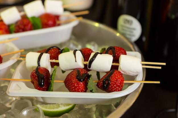 Zbliżenie kebabów deserowych z truskawkami i marshmallow, skropione czekoladą, podawane na jednorazowej tacy i chłodne w misce wypełnionej lodem