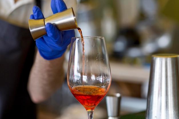 Zbliżenie kelner z maską przygotowuje napoje