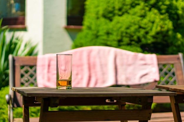 Zbliżenie kieliszek z napojem na dole na drewnianym stole