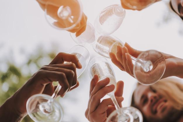 Zbliżenie: kieliszki do szampana clink w słońcu.