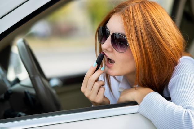Zbliżenie kierowcy młoda ruda kobieta korygująca makijaż z ciemnoczerwoną szminką patrząc w lusterko wsteczne samochodu za kierownicą pojazdu.