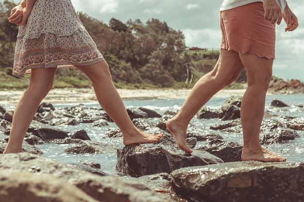 Zbliżenie kilku przyjaciół cieszących się czasem spacerując po skałach nad falującym oceanem
