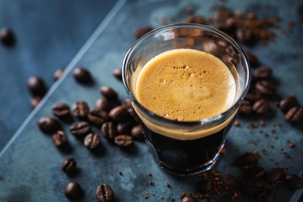 Zbliżenie klasycznego świeżego espresso na ciemnej powierzchni.