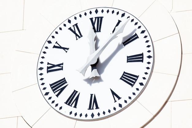 Zbliżenie klasyczny czarno-biały zegar na kamiennej ścianie