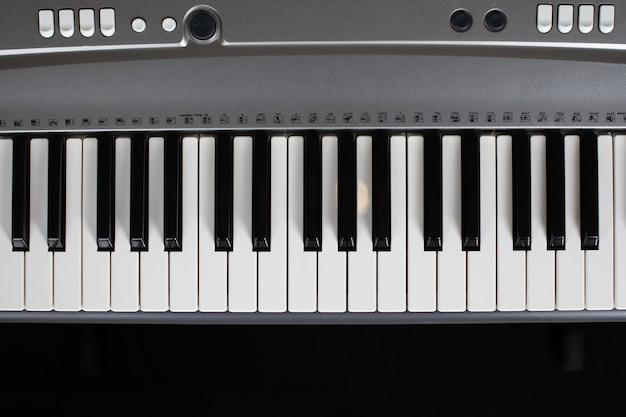 Zbliżenie klawiszy szarego elektronicznego syntezatora, widok z góry