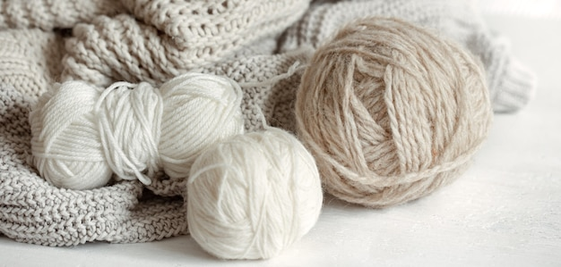 Zbliżenie kłębków włóczki w pastelowych kolorach i przytulnego swetra z dzianiny