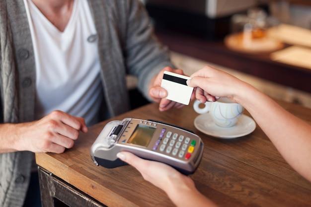 Zbliżenie klienta płacącego kartą kredytową