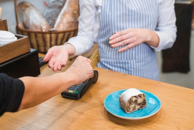 Zbliżenie klienta za pomocą terminala płatniczego za zapłacenie rachunku za ciasto