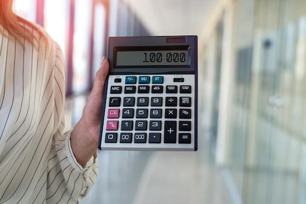 Zbliżenie: kobieca ręka trzyma kalkulator nad nowoczesnym centrum. koncepcja finansów i rachunkowości