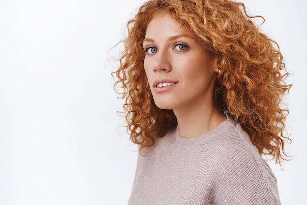 Zbliżenie kobieca wspaniała rudowłosa kędzierzawa kobieta w beżowej bluzce stojąca na wpół odwrócona na białej ścianie, odwróć głowę do aparatu ze zmysłowym, szczęśliwym i kokieteryjnym wyrazem, flirtując