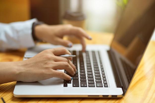 Zbliżenie kobiece dłonie piszące, przeglądające, wykonujące zadania na klawiaturze laptopa na drewnianym stole