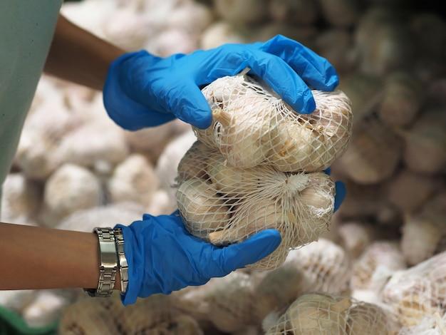 Zbliżenie. kobiece dłonie w niebieskich rękawiczkach biorą czosnek w supermarkecie podczas pandemicznego koronawirusa covid-19.